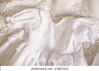 White christening gown lying on the handmade laces. Baptism. Religion.