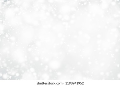 White Christmas abstract bokeh background with snowflake and silver glittering bokeh stars. Festive Glowing blurred lights