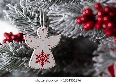 white Christmas angel on a tree. Wooden angel on the Christmas tree. Macro photo.