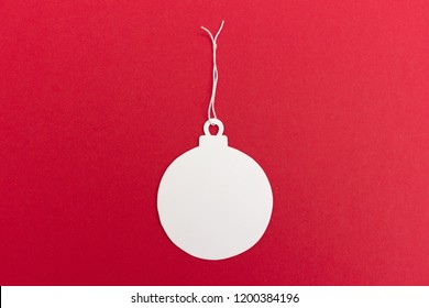 White christmas ball ornament paper tag on bright red background