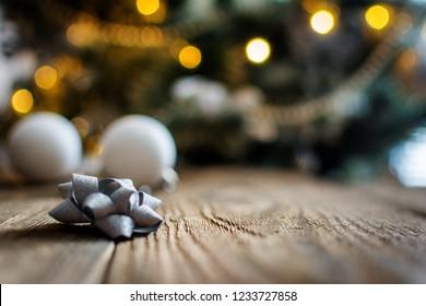 White Christmas bulbs on wood table and christmas tree