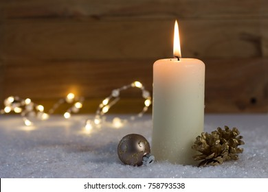 white christmas candle with cones and christmas ball on snow underground in front of wooden background
