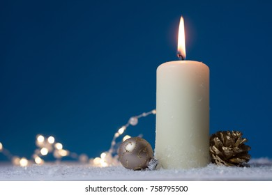white christmas candle with golden christmas ball and cone on snow underground and blue background