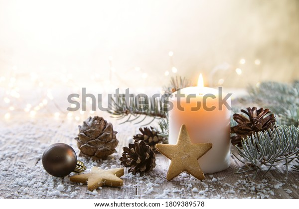 White Christmas candle on rustic wooden boards - Decoration with natural elements, twigs, pine cones and cookies.