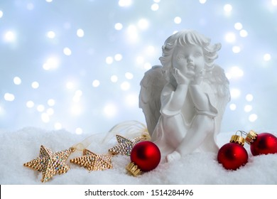 White christmas - cute angel in snow , blue night with lights in background. Happy Christas and holidays concept.
