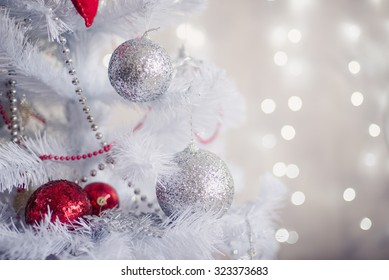 White Christmas decoration with balls on fir branches with blurred background