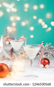 White Christmas eggnog drinks with candy canes and straws in a colorful setting with sparkling lights on a teal background