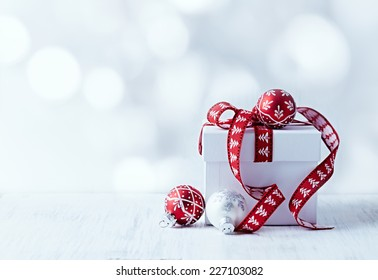 White Christmas Gift with Red Ribbon and Christmas Balls. Copy-space