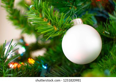 A white Christmas ornament hangs on a tree