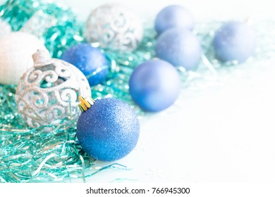 White christmas ornaments on light blue background with colorful bokeh lights. Merry christmas card. Winter holiday xmas theme. Space for text. Happy New Year.