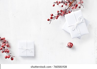 White Christmas Presents with Red Christmas Decorations on painted wood; flat lay arrangement. Symbolic image. Christmas background. White background. Copy space. Top view.