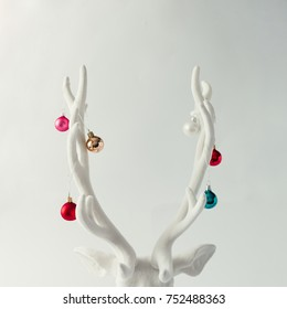 White Christmas reindeer head with antlers with christmas baubles. New Year concept.