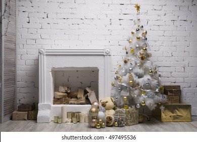 White Christmas tree with golden and silver balls, gift boxes, holiday decorations equipped fireplace, brick wall background