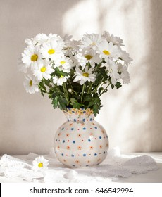 White chrysanthemum in a ceramic vase on a white background. Selective focus.