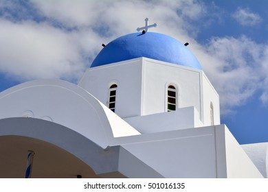 White church with blue cupola in Santorini, Greece