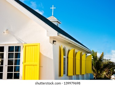 White church building with bright yellow window shudders in Hope Town, Abaco, Bahamas