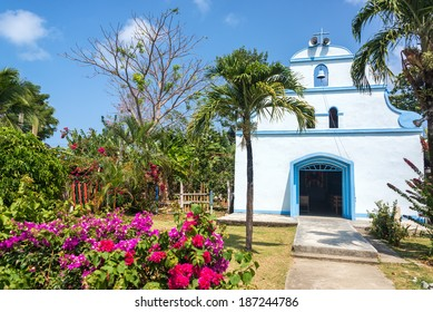 White church and colorful tropical flowers in Capurgana, Colombia