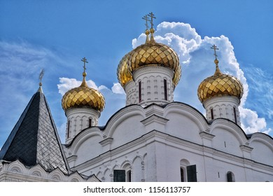 White church with golden domes against the blue sky with clouds. Isolated. Russia, Kostroma.
