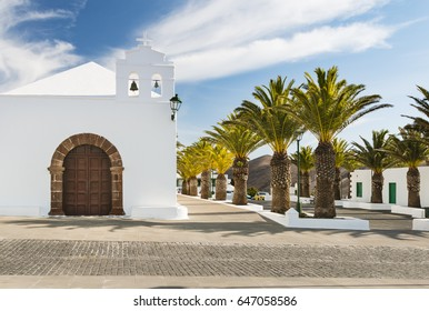 White church and palm trees in Femes in Lanzarote, Spain.