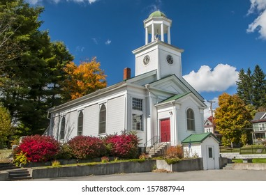 A white church with red doors in the autumn