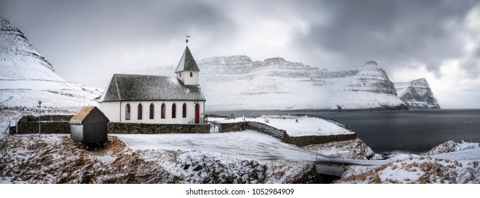 White church in snowy Vidareidi village with Bordoy and Kunoy islands in background, Faroe Islands