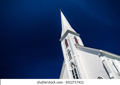 A white church steeple in front of a dark blue clear sky.