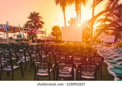 White cinema screen for projector in front of rows of chairs. Tropical scene at hotel resort at sunset.