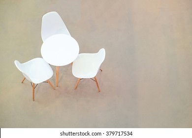 White circle table and chairs on carpet floor. view from above