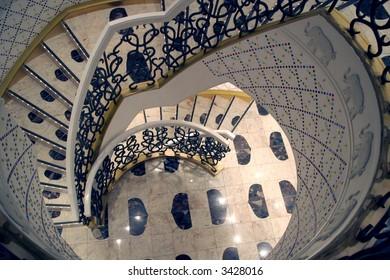 A white circular staircase descending into the distance