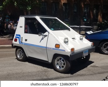 White Citicar 1970's electric car on display at First Saint Paul's Lutheran Church Collector Car Show on Goethe Street, Chicago, IL July 8th, 2018