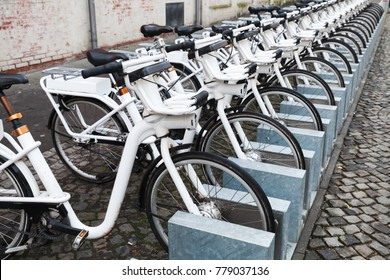 White city bicycles for rent stand in a row on a cobbled street of Copenhagen, Denmark