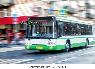 white city bus goes along street