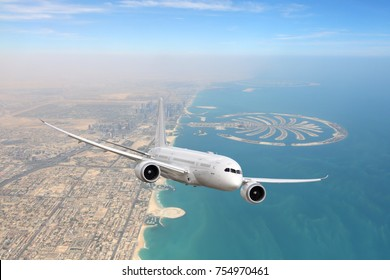 White civil twin-engine passenger airliner flying above Dubai city and coastline.
