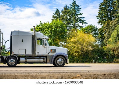 White classic big rig industrial professional semi truck with vertical pipes and horns on the roof transporting cargo in covered bulk semi trailer running on the flat highway road with green trees