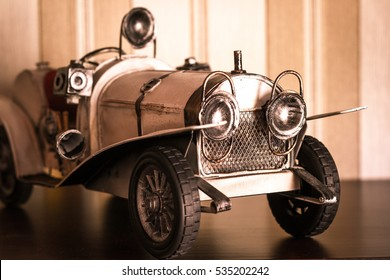 White classic car model over brown stripped wallpaper
