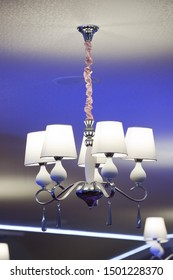 White classic chandelier with lampshades on the ceiling. Included chandelier on the ceiling.