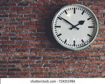 White classic clock hang isolated on red brick wall background. Simple design and decoration background. Old memories which reflects on the old clock surface.