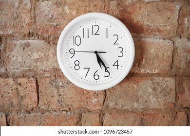 White classic clock on red brick wall. Twenty five minutes past five