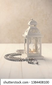 White classic decorative lantern or candle holder with prayer beads.