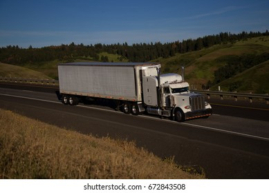 White Classic Peterbilt pulling a white unmarked trailer along a rural Oregon Highway.  June 20th, 2017 Rural Oregon, USA