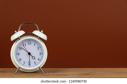 white classic style alarm clock on wooden table - 4:30 o'clock