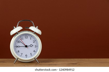 white classic style alarm clock on wooden table - 2:45 o'clock