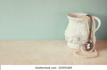 white classic victorian vase on wooden table with a collection of romantic vintage jewelry and pearls. retro filtered image. room for text