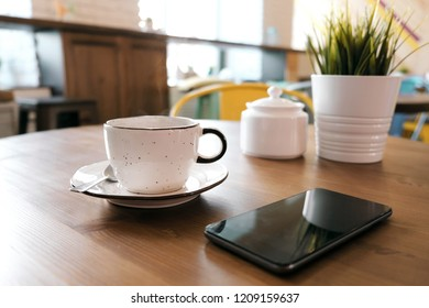 A white clay cup with coffee stands on a wooden table, next to it is a smartphone and a green flower in a pot. Blur cafeteria as background.