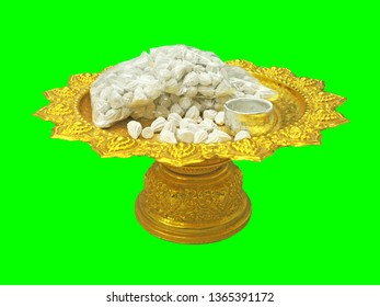 White clay filler place on golden tray with pedestal as equipment for Thailand Songkran festival isolated on green background