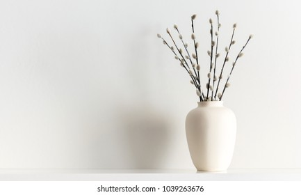 White clay vase on the shelf with spring flowers, branches of the pussy willow, on a white wood background. Space for text.