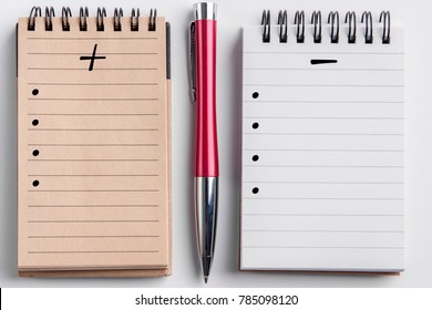 White clean background with a small circle pad with white lined sheets, a small notebook with beige lined pages and a red and silver elegant pen and pluses and minuses list