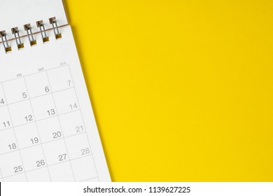 White clean calendar on solid yellow background with copy space, business meeting schedule, travel planning or project milestone and reminder concept.
