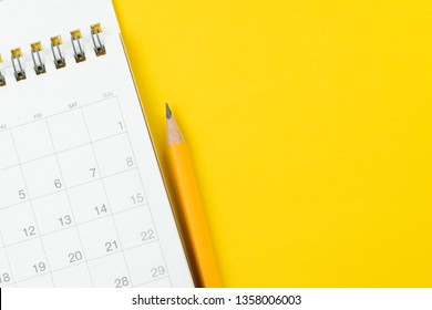 White clean calendar with yellow pencil on solid yellow background with copy space using as reminder, schedule or business project plan and timeline concept.