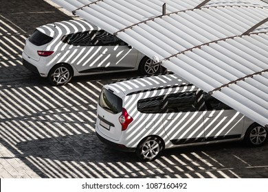 white clean cars on a parking lot in sunny summer day. the shadows from the canopy falling on vehicles